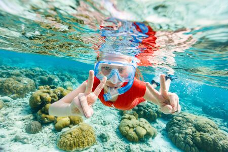 Underwater photo of a little girl swimming and snorkeling in tropical ocean