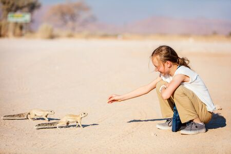 Adorable girl and little ground squirrels in Namibia