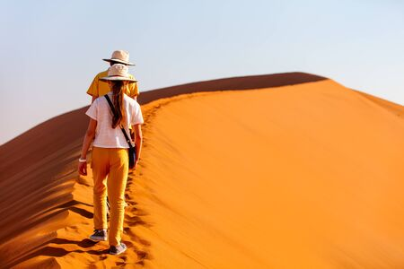 Kids brother and sister climbing up famous red sand dune Big Daddy  in Sossusvlei Namibia Archivio Fotografico