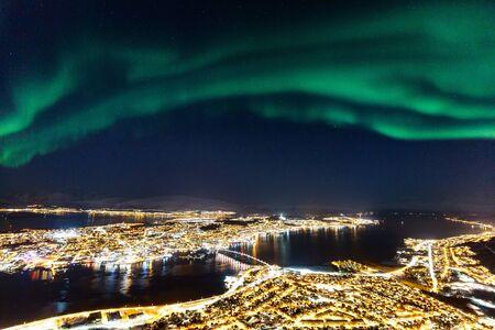 Niesamowita aktywność zorzy polarnej Aurora Borealis nad miastem Tromso w północnej Norwegii
