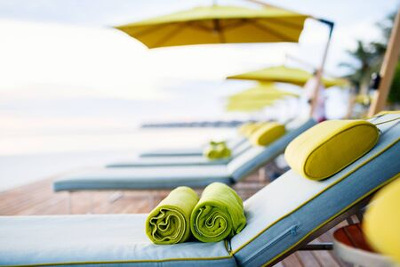 Rolled up towels on sunbeds by beautiful luxury swimming pool at hotel resort