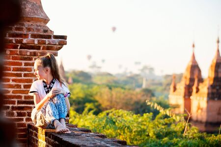 Young girl enjoying rooftop view of hot air balloons fly over thousands of ancient pagodas at sunrise in Bagan Myanmar