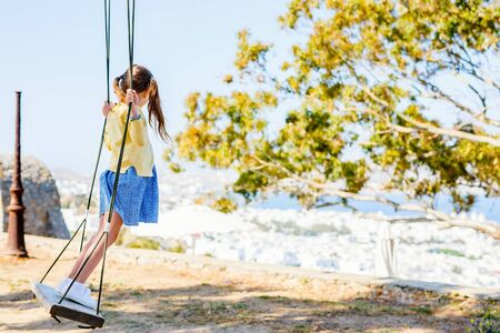Cute little girl having fun on a swing outdoors on summer day