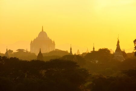 Scenic sunset with Ananda temple silhouette and thousands of historic buddhist pagodas and stupas in Bagan Archeological area in Myanmar