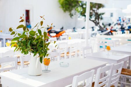 Typical greek traditional village on Mykonos Island, Greece, Europe with empty outdoor restaurant tables on street without tourists