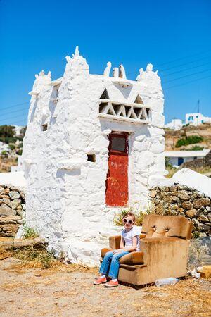 Adorable little girl enjoying views of traditional white village on Mykonos island