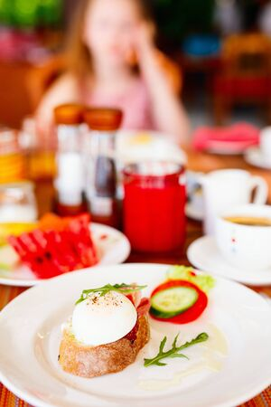 Poached eggs served for breakfast with bruschetta, vegetables, coffee and juice