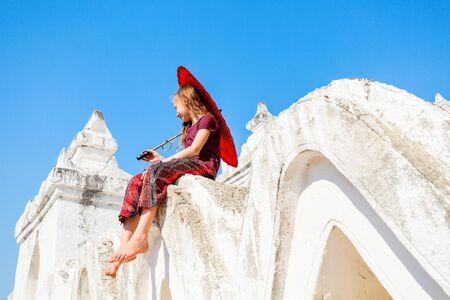 Young girl with traditional burmese umbrella at beautiful white Hsinbyume pagoda in Mingun Myanmar