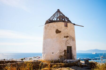Old greek windmill overlooking traditional village on Mykonos Island, Greece, Europe