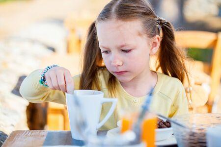 Adorable little girl at breakfast in restaurant
