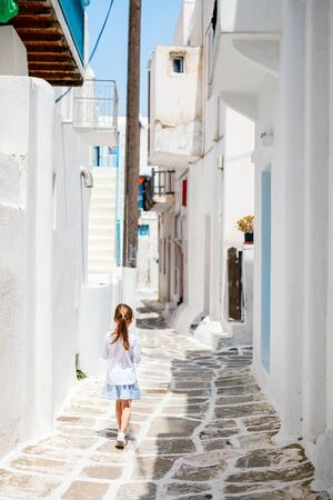 Back view of little girl at typical greek traditional village with white houses and colorful doors on Mykonos Island, Greece, Europe