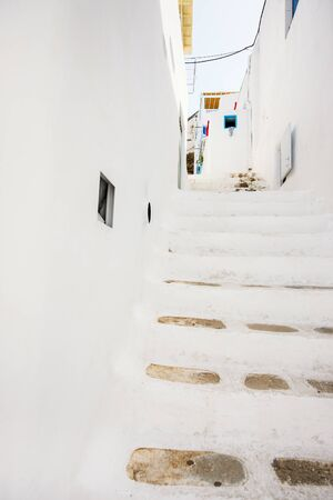 Typical greek traditional village with white stairs, walls and colorful doors and windows on Mykonos Island, Greece, Europe