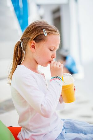 Adorable little girl drinking fresh smoothies at outdoor cafe on summer day