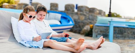 Brother and sister looking together at screen of tablet device at outdoor terrace on summer day Stockfoto
