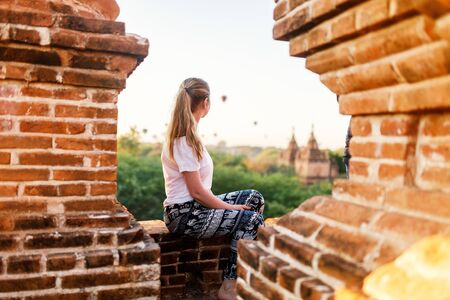 Beautiful woman enjoying rooftop view of hot air balloons fly over thousands of ancient pagodas at sunrise in Bagan Myanmar