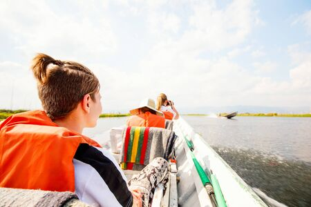 Back view of family with two kids exploring Inle lake in Myanmar