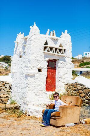 Cute teenage tourist enjoying views of traditional white village on Mykonos island