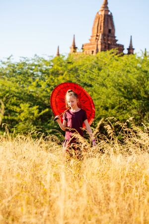 Young girl with traditional burmese parasol visiting ancient temples in Bagan Myanmar Stockfoto