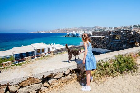 Back view of little girl enjoying views of Mediterranean sea on Mykonos island, Greece Stockfoto