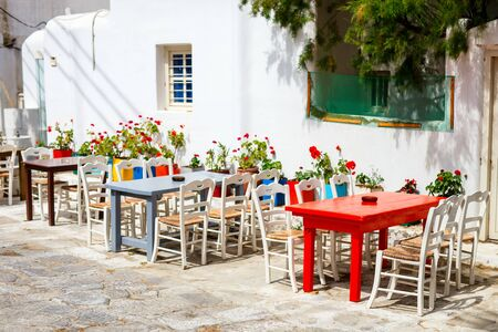 Typical greek traditional village on Mykonos Island, Greece, Europe with empty outdoor restaurant tables on street without tourists Stockfoto