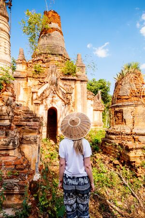 Back view of young woman visiting hundrets of centuries old stupas in Indein near lake Inle in Myanmar Stockfoto