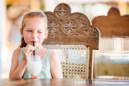 Portrait of adorable little girl drinking milkshake