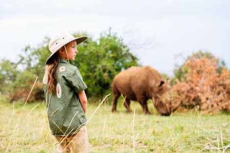 Cute little girl on walking safari in Kenya observing white rhinos