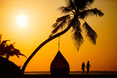 Silhouettes of romantic couple on tropical beach at sunset 写真素材 - 152343016