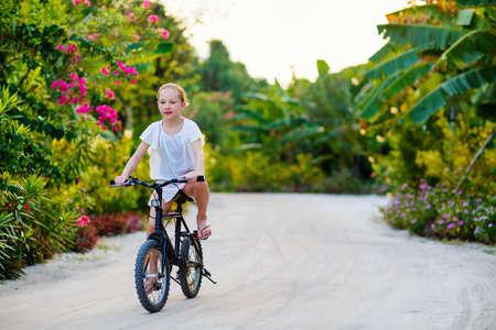 Cute girl biking at tropical island settings having fun Zdjęcie Seryjne