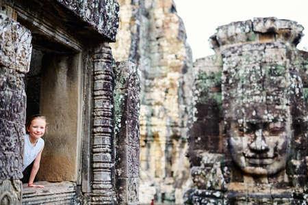 Little girl in beautiful ancient Bayon temple in Siem Reap Cambodia Zdjęcie Seryjne