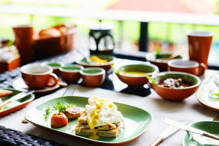 Breakfast table filled with assorted food.  Poached eggs, Sri lankan curry and tea
