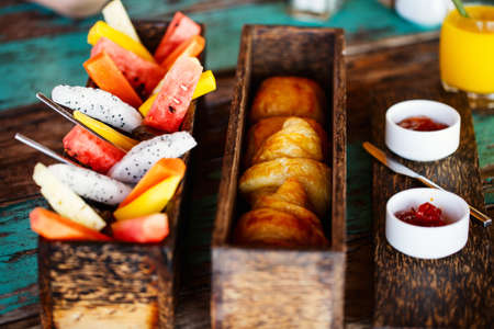 Close up of delicious organic food served for breakfast on rustic wooden table. Fruits, juice, croissants and jam flat lay.