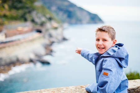 Little boy enjoying scenic view of colorful Vernazza village, Cinque Terre, Italy