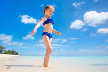 Adorable little girl at beach enjoyong tropical summer vacation