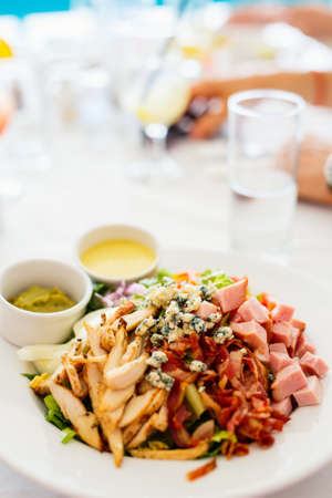 Delicious Cobb salad with tomatoes, lettuce, crisp bacon, chicken breast, hard-cooked eggs, avocado and cheese served for lunch at restaurant Zdjęcie Seryjne