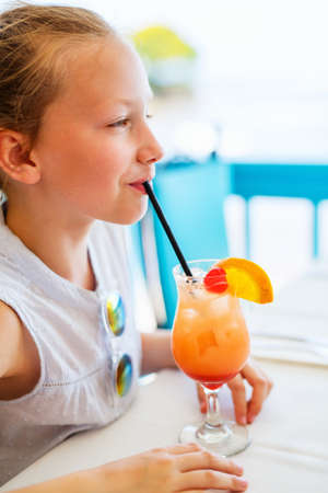Adorable little girl drinking tropical juice mocktail at outdoor cafe on summer day Zdjęcie Seryjne