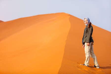 Cute little girl surrounded by red dunes in Sossusvlei in Namibia Zdjęcie Seryjne