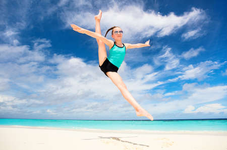 Happy girl jumping at tropical beach having a lot of fun on summer vacation Zdjęcie Seryjne