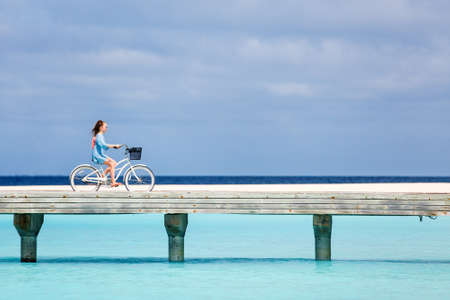 Cute girl riding bike on a jetty over tropical ocean enjoying active vacation