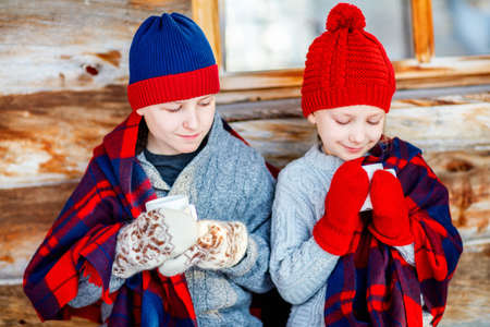 Kids outdoors on beautiful winter day drinking hot chocolate in front of log cabin vacation house Zdjęcie Seryjne - 155235523