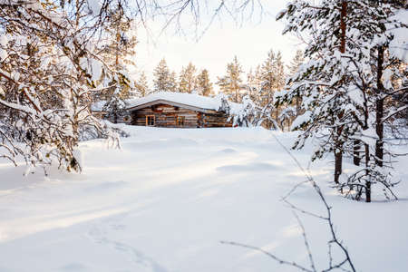 Beautiful winter landscape with wooden hut and snow covered trees in Finnish Lapland forest 写真素材 - 155235617
