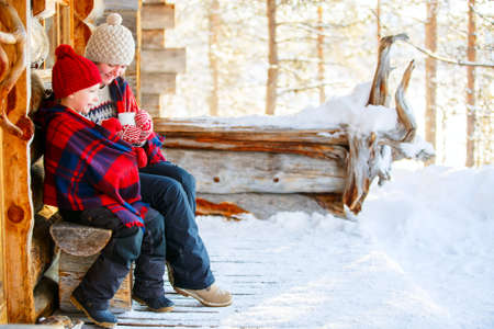 Beautiful family of mother and her little daughter with hot drinks enjoying snowy winter day outdoors