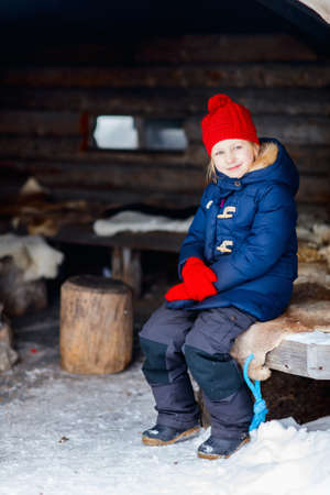 Little girl outdoors on beautiful winter day in front of log cabin