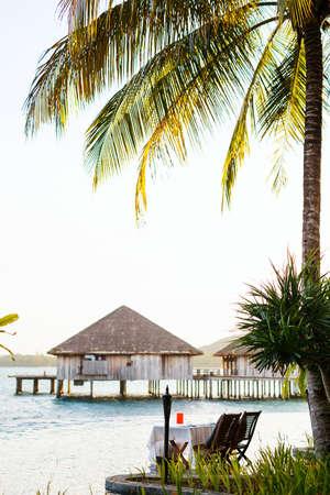 Romantic sunset dinner setting  near infinity swimming pool at luxury tropical resort