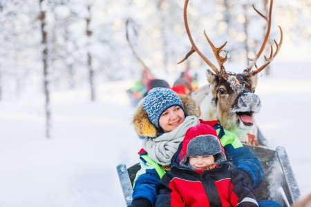 Family of mother and little girl at reindeer safari in winter forest in Lapland Finland Zdjęcie Seryjne - 155367376
