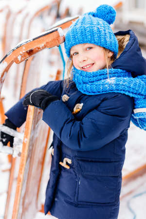 Adorable little girl wearing warm clothes outdoors on beautiful winter snowy day Zdjęcie Seryjne - 155235600