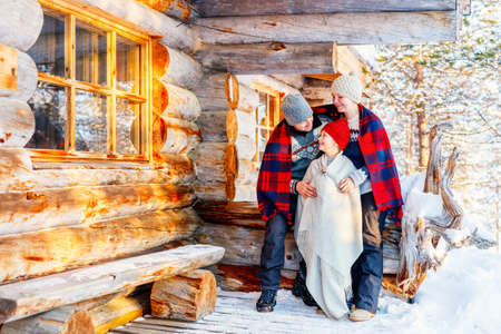 Family with child outdoors on beautiful winter day in front of log cabin vacation house 写真素材 - 155367379