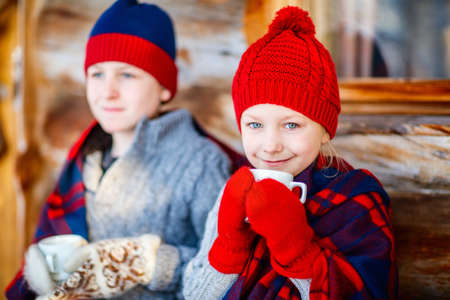 Kids outdoors on beautiful winter day drinking hot chocolate in front of log cabin vacation house 写真素材