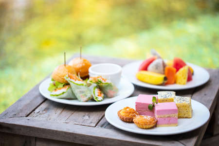 Room service delicious lunch burgers, fruits and sweets served on a table near swimming pool Zdjęcie Seryjne - 155367381