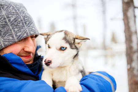 Man holding a husky puppy in Lapland Finland